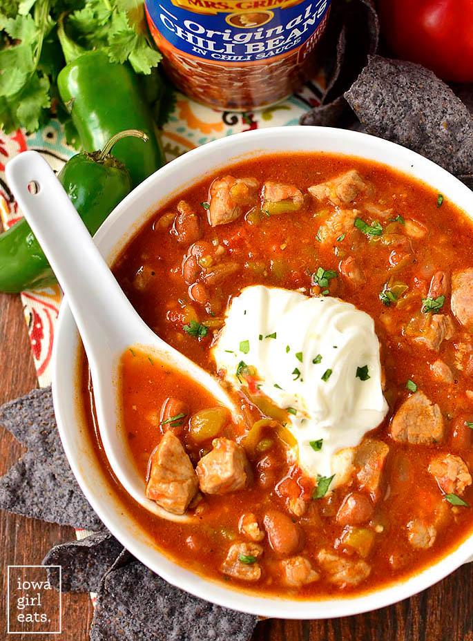 a big white spoon in a bowl of pork fiesta chili