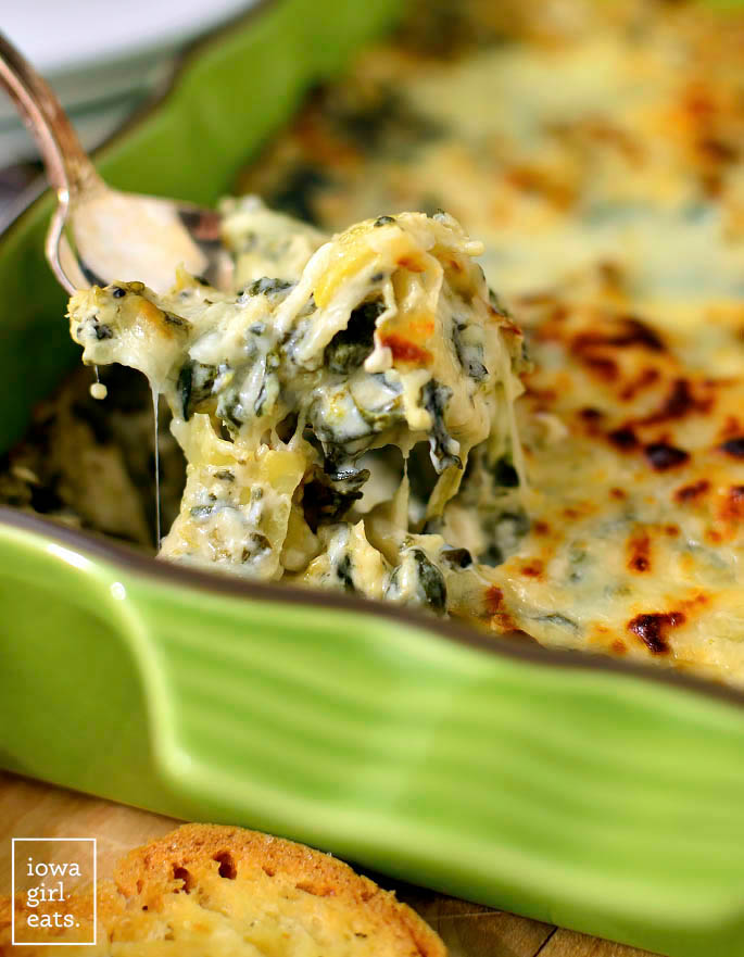 spoon scooping caesar spinach and artichoke dip from a baking dish