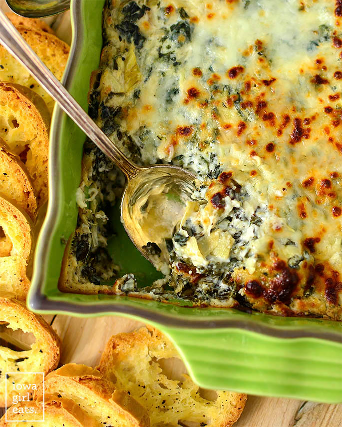 serving spoon in a dish of caesar spinach and artichoke dip