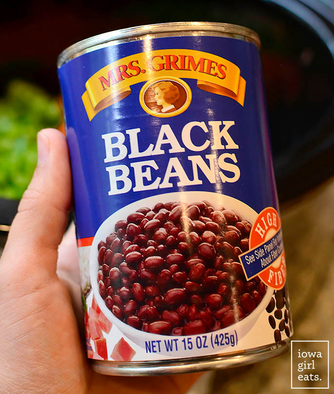 a hand holding a can of mrs grimes black beans