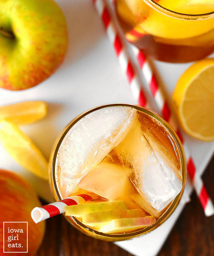 overhead photo of a sparkling maple bourbon cider in a glass with apple garnish