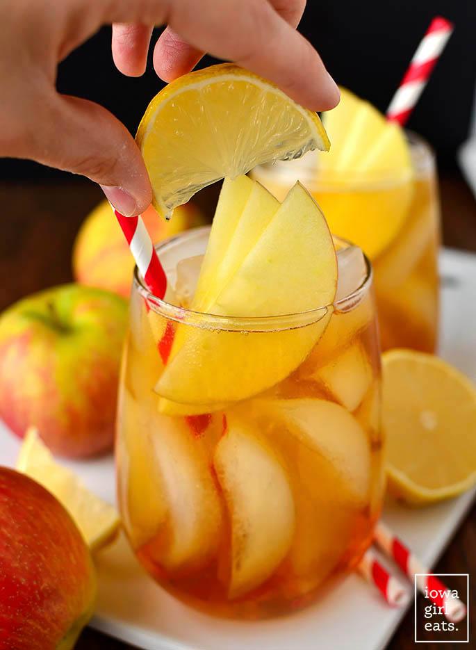 hand squeezing a lemon wedge into a bourbon cider