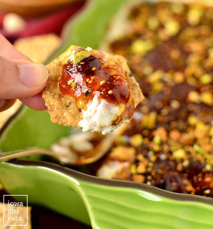 a crunchy cracker dipping into a baking dish of warm fig and prosciutto goat cheese dip