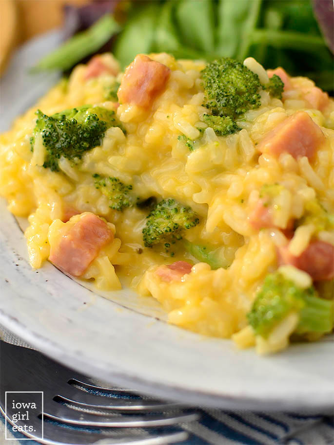 cheesy ham and broccoli rice on a plate with a bite taken out of it
