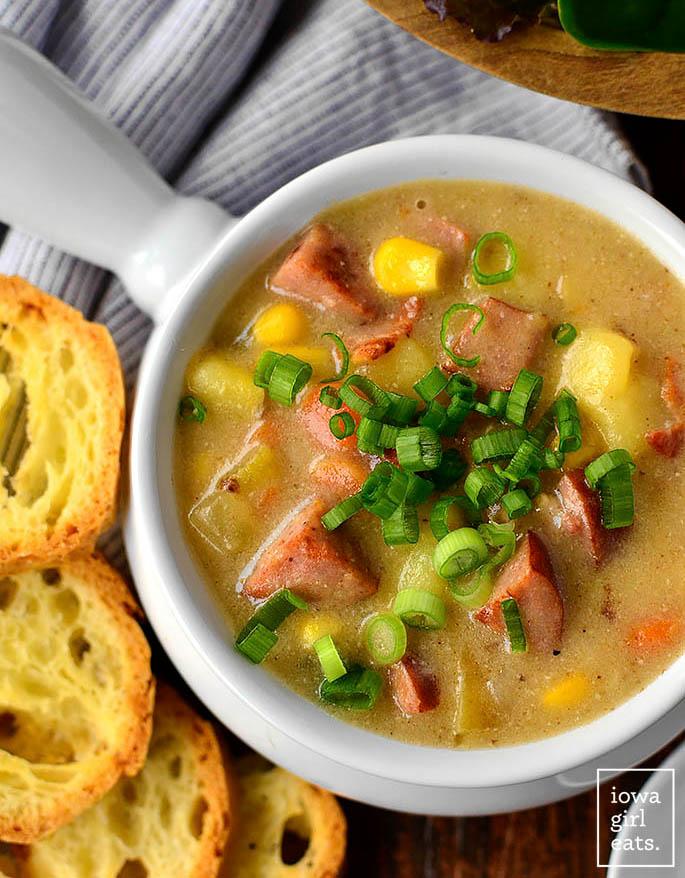 bowl of sweet corn kielbasa and potato soup with chopped green onions on top