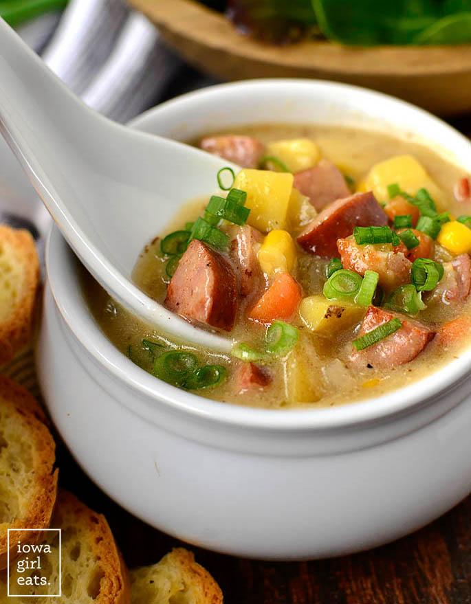 spoon taking a bite of sweet corn kielbasa and potato soup