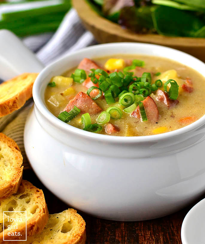 sweet corn kielbasa and potato soup in a bowl with green onions on top