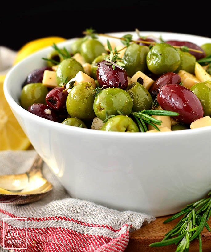 herb and garlic marinated olives and cheese in a serving bowl
