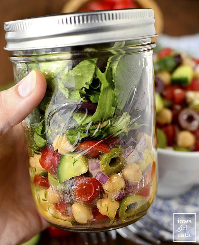 Hand holding mason jar of salad