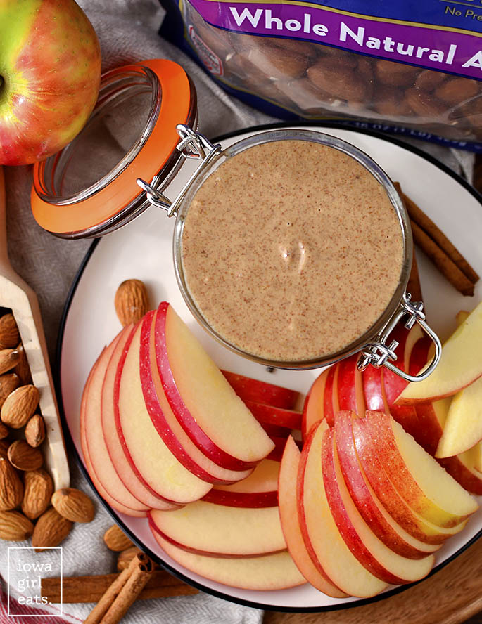 Jar of Snickerdoodle Almond Butter with sliced apples.