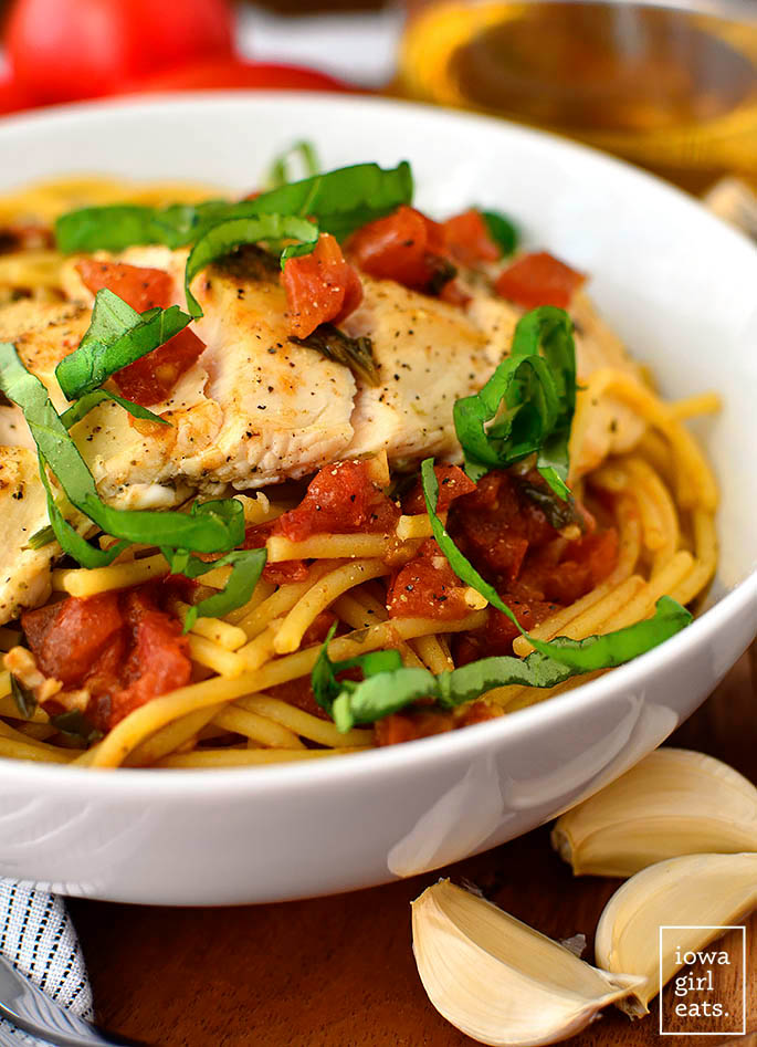 close up of chicken bruschetta pasta in a bowl with fresh basil