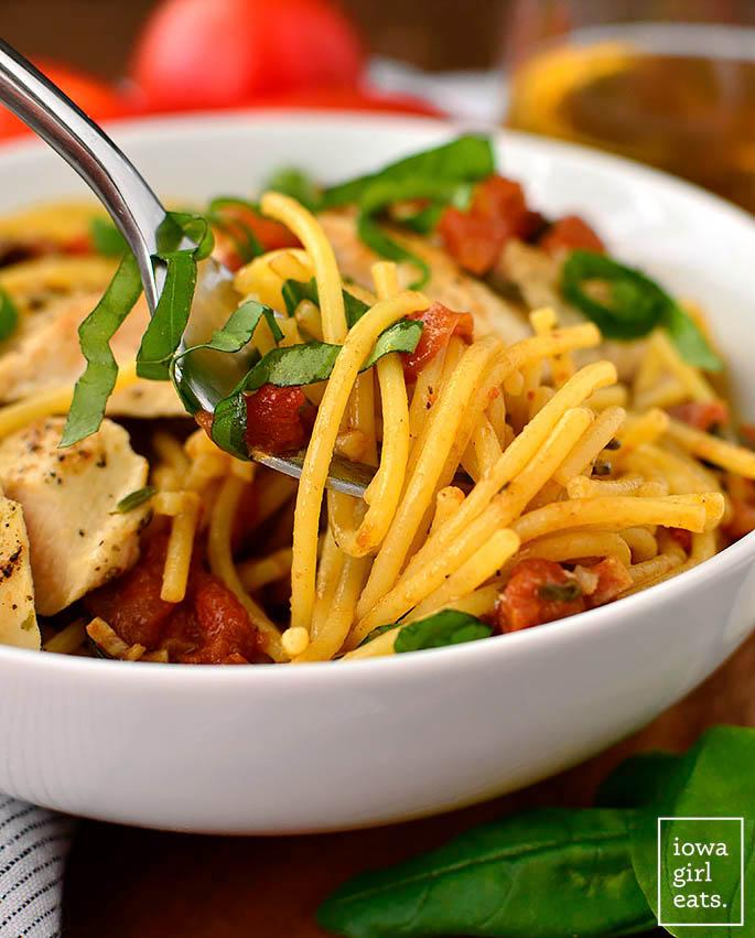 fork twirling pasta with chicken and bruschetta