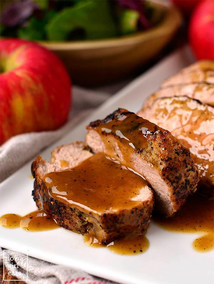 pan roasted pork tenderloin slices on a platter with a cider glaze