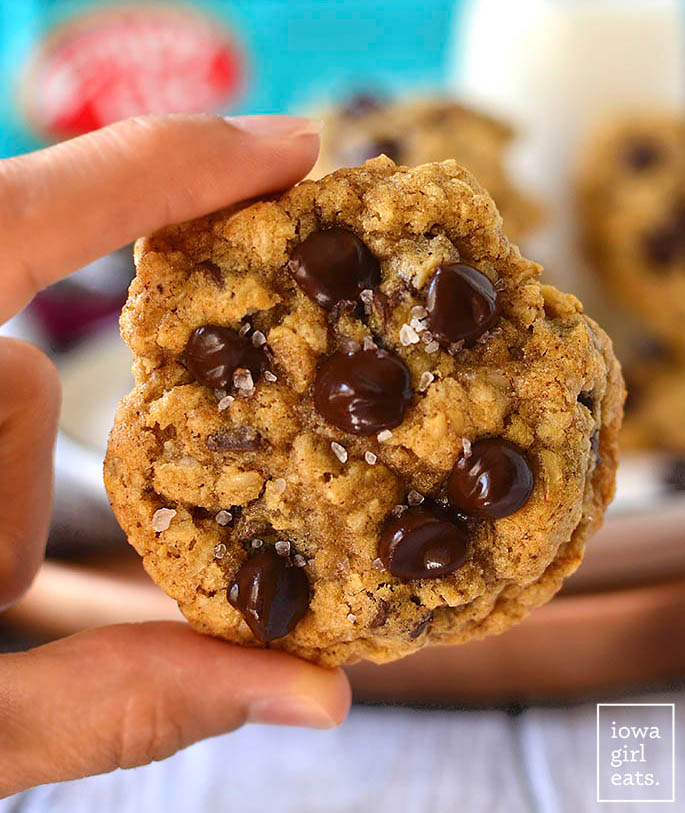 hand holding a brown butter oatmeal chocolate chip cookie
