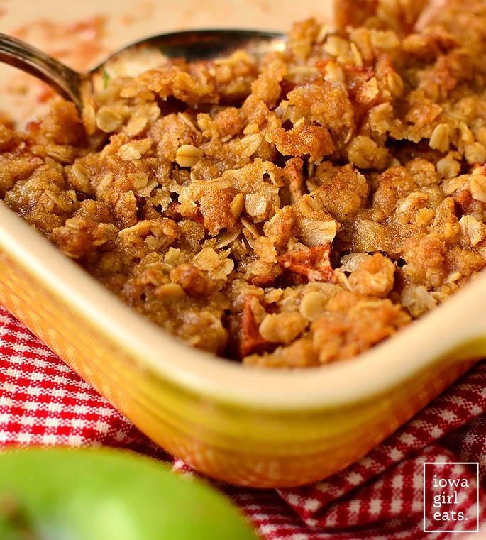 baking dish of gluten free apple crisp with a serving spoon inside