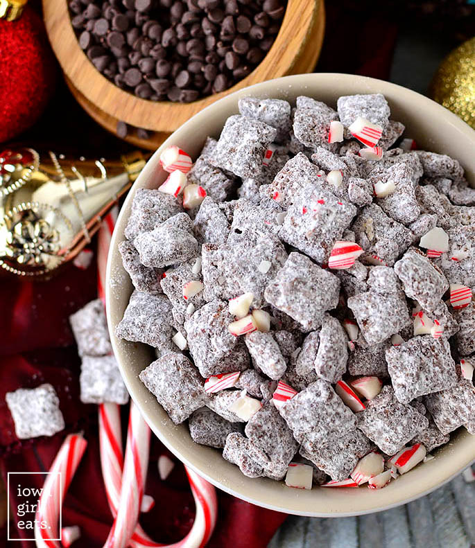 chocolate peppermint puppy chow in a large bowl with crushed candy canes