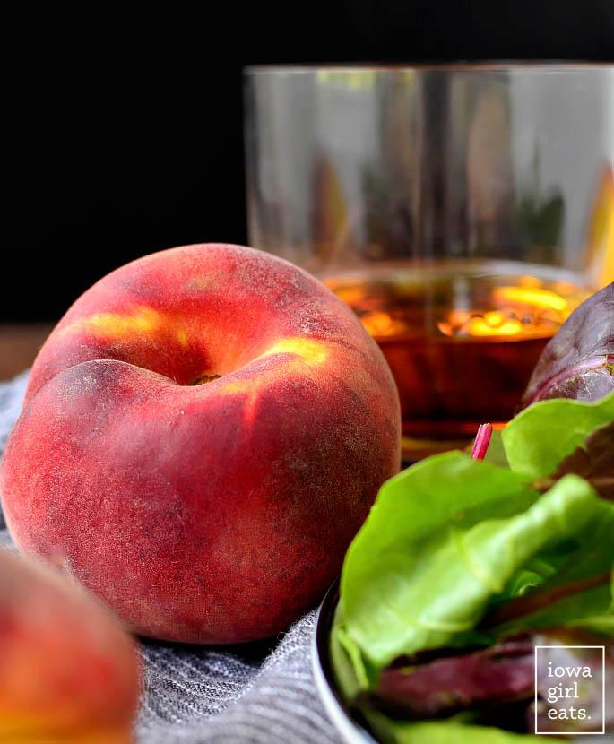 fresh peach next to a glass of bourbon