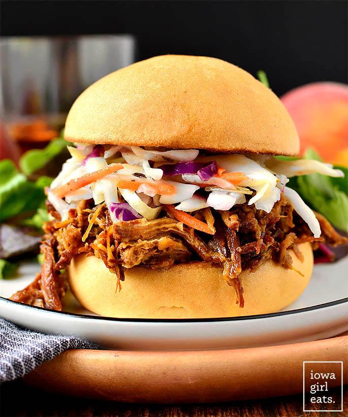 crock pot peach and bourbon shredded pork sandwich on a bun with slaw