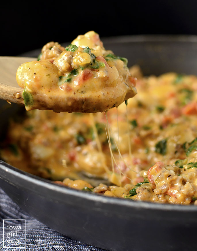 Spoon scooping Cheesy Gnocchi Florentine out of a skillet