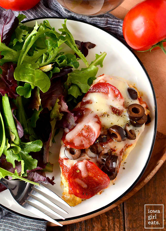 Overhead photo of a piece of Pizza Chicken on a plate with a salad