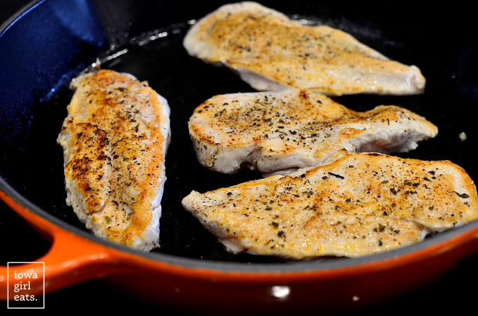 chicken cutlets cooking in a skillet