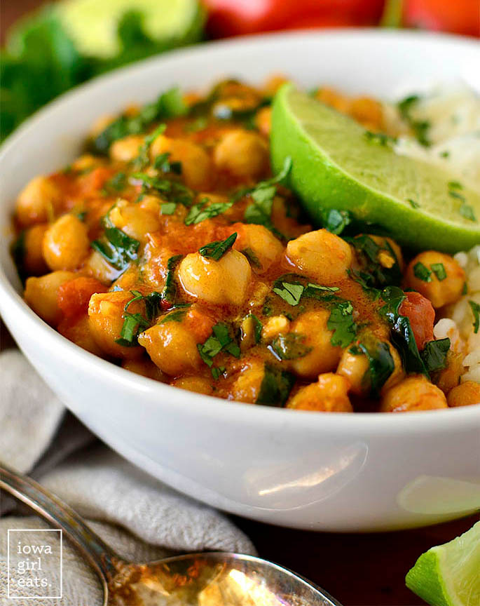 vegan chickpea curry in a bowl with cilantro and lime