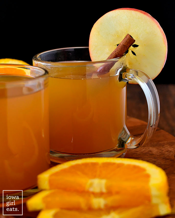 mulled cider in glasses with cinnamon and apple slices