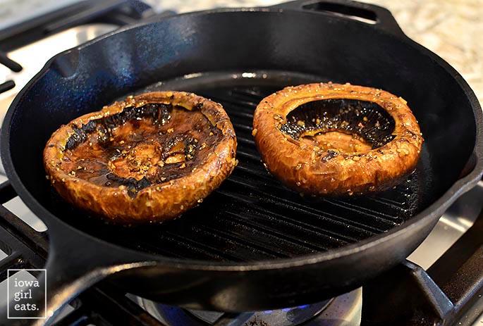 Portobello mushrooms grilling in a grill pan