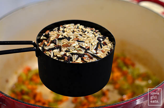 a cup of wild rice being added to a pot of soup