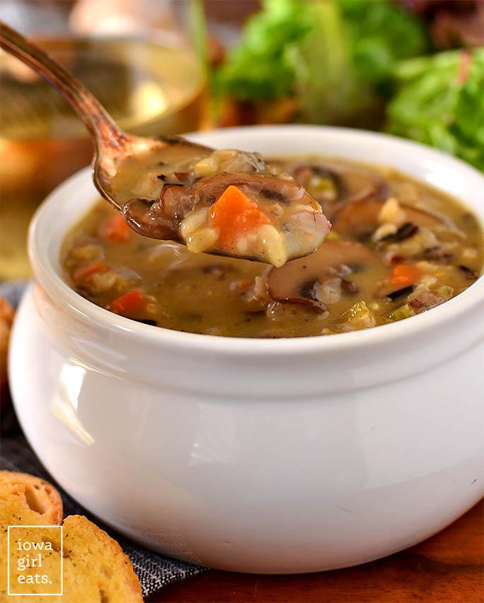 a spoon taking a bit of wild rice mushroom soup