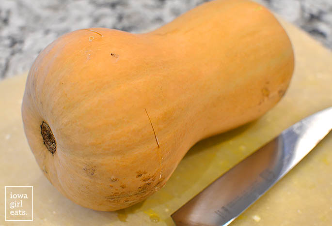 a butternut squash that has been pierced with a knife in the bulb end on a cutting board