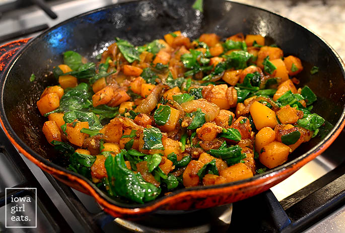 onions, spinach, and butternut squash caramelizing in a skillet