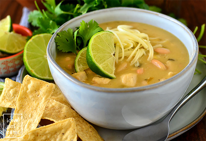 Bowl of green chicken enchilada soup with lots of toppings