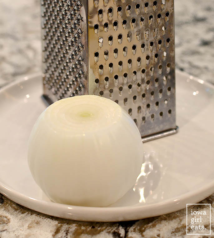 a peeled onion sitting on a plate with a grater