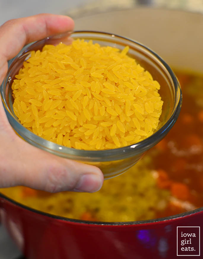 hand holding a bowl of dry gluten free orzo about to be put in a pot