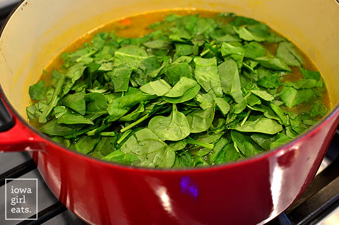 fresh baby spinach being added to a pot of homemade Italian wedding soup